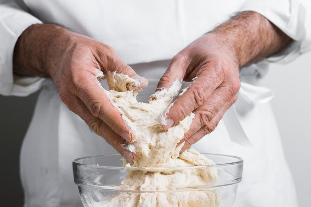 Mãos masculinas sovando massa de pão.